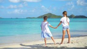 Små lyckliga roliga flickor har mycket gyckel på den tropiska stranden som tillsammans spelar Solig dag med regn i havet stock video