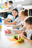 små lyckliga skolflickor som tar lunch arkivfoto
