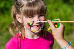 Små lyckliga systrar spelar med färger i parkera, barnlek, barn målar sig Royaltyfri Fotografi