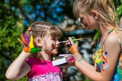 Små lyckliga systrar spelar med färger i parkera, barnlek, barn målar sig Royaltyfria Bilder