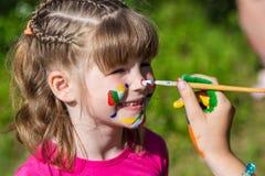 Små lyckliga systrar spelar med färger i parkera, barnlek, barn målar sig Royaltyfria Foton