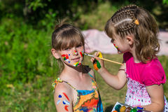 Små lyckliga systrar spelar med färger i parkera, barnlek, barn målar sig Royaltyfri Bild