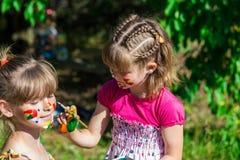 Små lyckliga systrar spelar med färger i parkera, barnlek, barn målar sig Arkivfoton