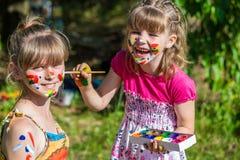 Små lyckliga systrar spelar med färger i parkera, barnlek, barn målar sig Arkivbilder