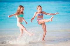 Små lyckliga ungar har mycket gyckel på den tropiska stranden som tillsammans spelar på grunt vatten Royaltyfria Foton