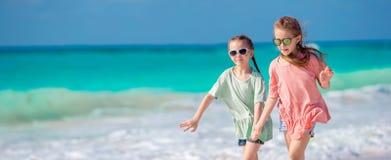 Små lyckliga ungar som har mycket gyckel på den tropiska stranden som tillsammans spelar Förtjusande flickor som dansar på den ka royaltyfria foton