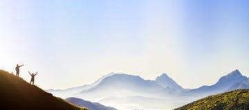 Små mörka konturer av turist- handelsresande på brant berglutning på soluppgång på kopieringsutrymmebakgrund av dalen som täckas  fotografering för bildbyråer