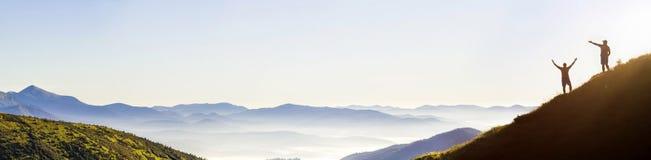 Små mörka konturer av turist- handelsresande på brant berglutning på soluppgång på kopieringsutrymmebakgrund av dalen som täckas  arkivfoto