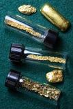 Små medicinflaskor av guldstoft och guld- klumpar Royaltyfria Bilder