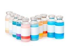 Små medicinflaskor med kulöra vikter Royaltyfria Bilder