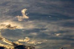 Små moln ovanför bergen på solnedgången royaltyfria foton