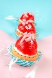 Små muffin med kräm- och jordgubbeglasyr Royaltyfri Bild