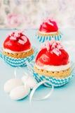Små muffin med kräm- och jordgubbeglasyr Royaltyfria Foton