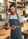 Små och medelstora företagägare på hans coffee shop genom att använda den digitala minnestavlan arkivfoton