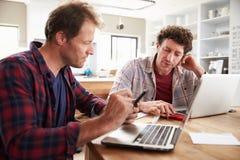 Små och medelstora företagpartners som hemma använder datorer royaltyfri bild
