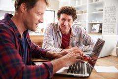 Små och medelstora företagpartners som hemma använder datorer Arkivbilder