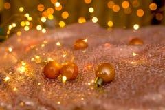 Små orange julbollar på härlig skinande bakgrund royaltyfria bilder
