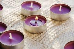 Små, purpurfärgade aromatiska stearinljus på en vit bakgrund arkivfoto