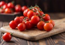 Små röda körsbärsröda tomater på lantlig bakgrund Cherrytomater på vinen Arkivbilder