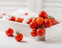 Små röda körsbärsröda tomater på lantlig bakgrund Cherrytomater på vinen Arkivfoto
