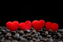 Små röda satänghjärtor på kaffebönor som isoleras på svart bakgrund, valentindag eller bröllopdag, firar royaltyfri fotografi
