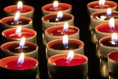 Små röda stearinljus i metallbunkar som bränner i mörkret royaltyfri fotografi