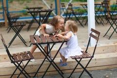 Små roliga flickor på det utomhus- kafét på varm sommar Arkivfoto