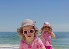 Små roliga systerflickor 3 och 4 gamla år på havswearinen royaltyfri bild