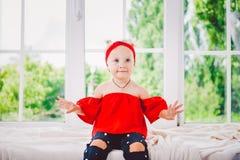 Små roliga två år gammalt flickabarn i stilfull röd kläder och jeans och gymnastikskor på fönsterbräda nära fönster Med ett leend arkivbilder