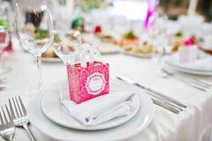 Små rosa färger boxas med godisar på tabellen på maträtt av bröllopgästen Arkivfoton