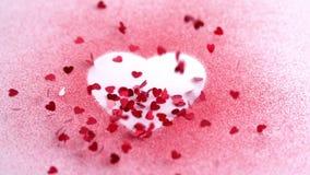 Små rosa konfettier som faller på en hjärta, drar stock video