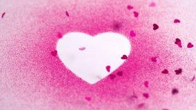 Små rosa konfettier som faller på en vit hjärta, drar stock video