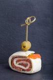 Små rullar med laxen, ost och pitabrödet på steknålen på en svart sl Royaltyfri Fotografi