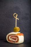 Små rullar med laxen, ost och pitabrödet på steknålen på en svart sl Arkivfoto