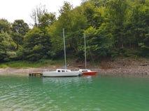 Små seglingyachter av kust- navigering förtöjas på pir i en pittoresk hamn Prestigefull och sund livsstil Recr royaltyfri foto