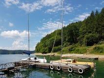 Små seglingyachter av kust- navigering förtöjas på pir i en pittoresk hamn Prestigefull och sund livsstil Recr arkivbilder