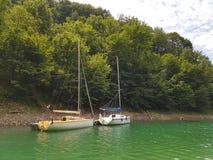 Små seglingyachter av kust- navigering förtöjas på pir i en pittoresk hamn Prestigefull och sund livsstil Recr royaltyfri fotografi