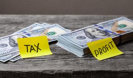 Små skatter på stora vinster, begrepp Kontorsklistermärkear på dollarräkningar på trätabellen arkivfoton