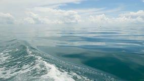 Små skummande blåa vågor efter ett fartyg och ett lugna hav i molnig dag Idyllisk tropisk waterscape Himlen reflekteras in arkivfilmer