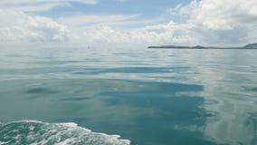 Små skummande blåa vågor efter ett fartyg och ett lugna hav i molnig dag Idyllisk tropisk waterscape Himlen reflekteras in lager videofilmer