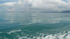 Små skummande blåa vågor efter ett fartyg och ett lugna hav i molnig dag Idyllisk tropisk waterscape Himlen reflekteras in stock video