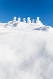 Små snögubbear figurerar anseendet på en bergstopp, copyspace i t royaltyfri fotografi