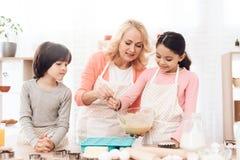 Små sonsonklockor som farmor hjälper hennes sondotter att hälla blandningen in i bakningformer fotografering för bildbyråer