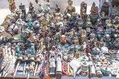 Små statyer, halsband och andra souvenirobjekt på försäljning på gatamarknadsplatsen royaltyfri foto