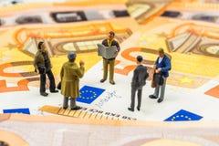 Små statyetter som diskuterar och står på nya 50 eurosedlar Arkivbild