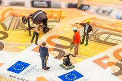 Små statyetter som hårt arbetar på nya 50 eurosedlar Arkivfoto