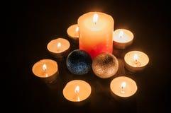 Små stearinljus runt om en större stearinljus och två juljordklot Royaltyfri Bild