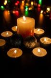 Små stearinljus runt om en större stearinljus och två juljordklot Arkivbilder