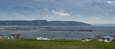 Små steniga öar och hem kura ihop sig i den kust- Bonavista byn längs kustlinjen Arkivfoto