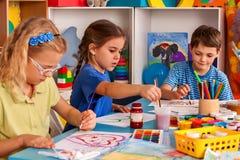 Små studentbarn som målar i konstskolagrupp Royaltyfri Bild